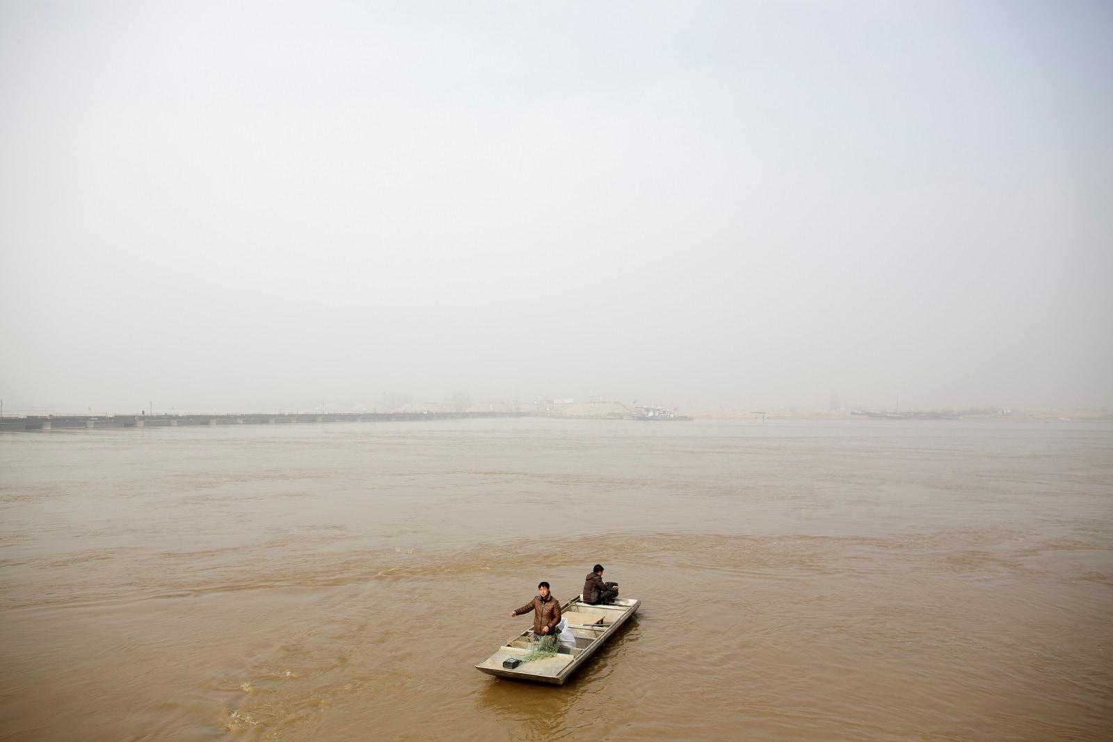 Fishermen Sun Lianxi, 32, and Sun Genxi, 44, travel down the Yellow River to cast their net on the northern outskirts of Zhengzhou, Henan province, China, February 21, 2019. REUTERS/Thomas Peter