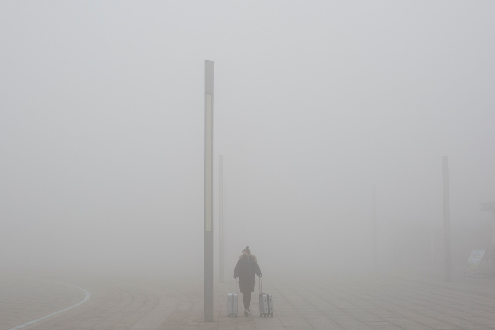 A woman walks outside a high-speed railway station on a hazy morning in Zhengzhou, Henan province, China February 21, 2019. REUTERS/Thomas Peter
