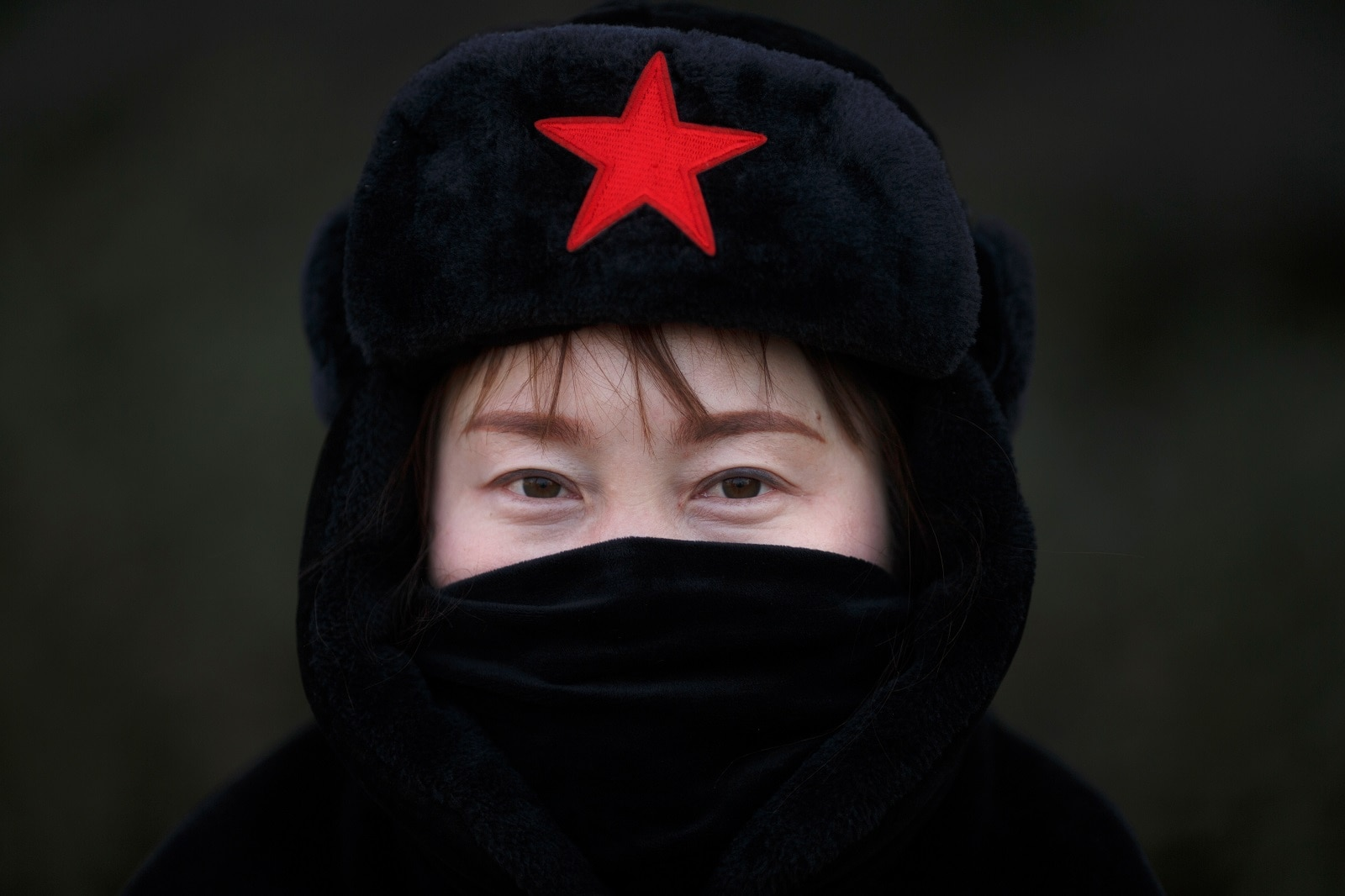 A driver of a tourist shuttle wears a hat with a red star as she poses for pictures at the Longmen Grottoes in Luoyang, Henan province, China January 21, 2019. REUTERS/Thomas Peter