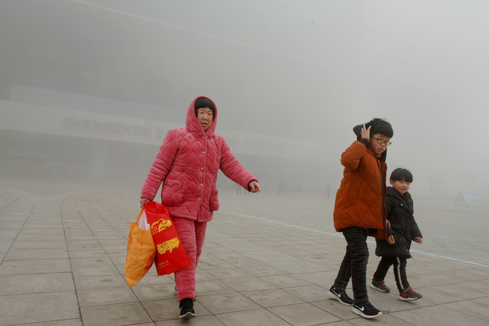 People leave the high-speed railway station on a hazy morning in Zhengzhou, Henan province, China February 21, 2019. REUTERS/Thomas Peter
