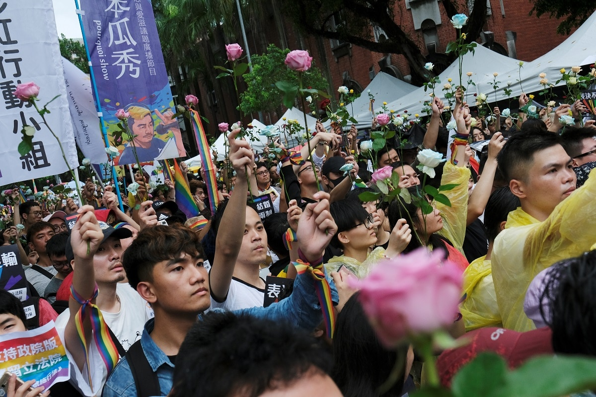 Same-sex marriage supporters hold roses to mourn those who committed suicide due to discrimination during a parliament vote on three draft bills of same-sex marriage law, outside the Legislative Yuan in Taipei. REUTERS/Tyrone Siu