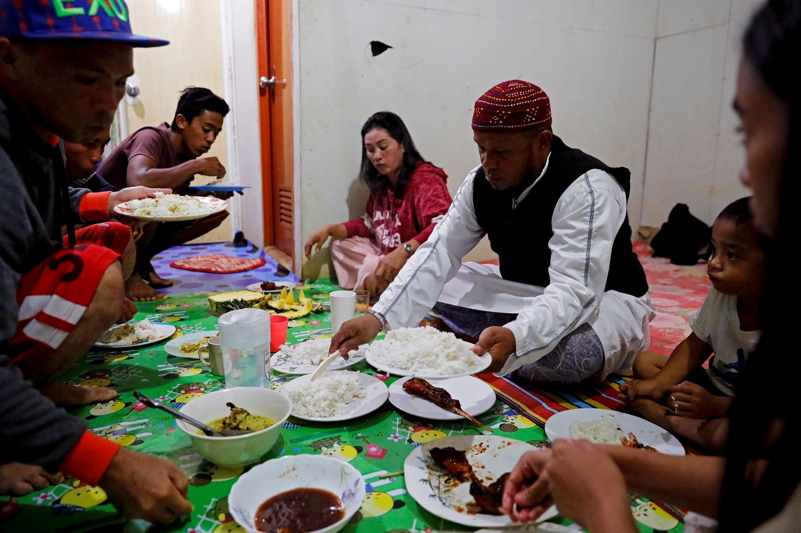 Mohammad Ali Acampong, 42, and his family breakfast with rice, chicken, and pineapples during ramadan in their temporary shelter in Marawi City, Lanao del Sur province, Philippines, May 12, 2019. REUTERS/Eloisa Lopez