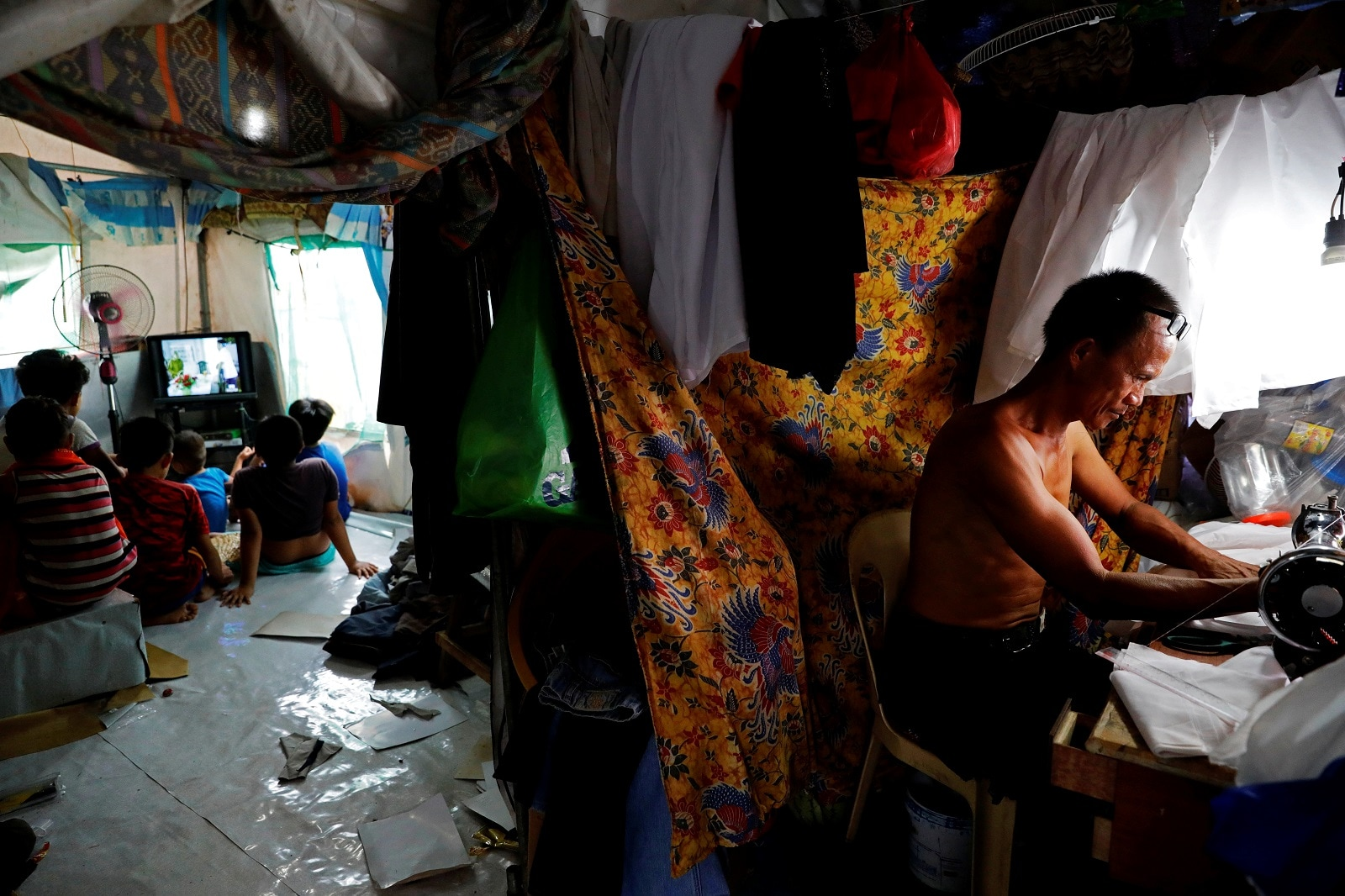 Abdul Gani, 49, works with a sewing machine as his children and nephews watch TV in a tent at an evacuation camp for families displaced by the Marawi siege, in Marawi City, Lanao del Sur province, Philippines, May 12, 2019. REUTERS/Eloisa Lopez