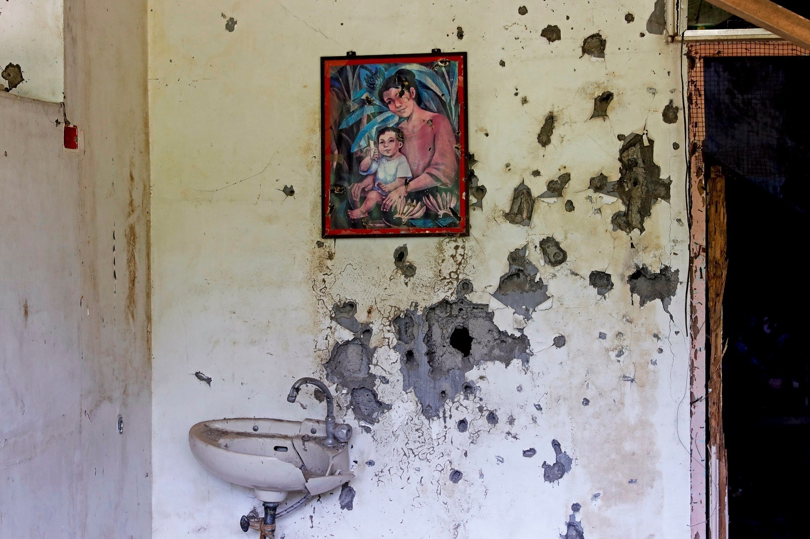 A painting of a mother and a child hangs on a wall at a bullet-riddled structure in Marawi City, Lanao del Sur province, Philippines, May 11, 2019. REUTERS/Eloisa Lopez