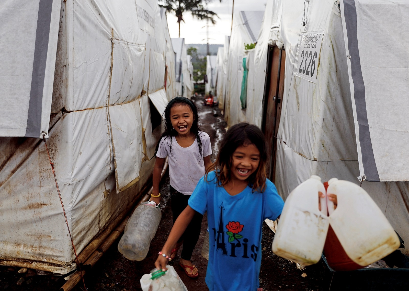 Girls carry water containers to be filled at an evacuation camp for families displaced by the Marawi siege, in Marawi City, Lanao del Sur province, Philippines, May 14, 2019. REUTERS/Eloisa Lopez
