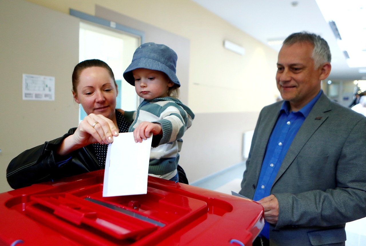 A woman holds a child as she casts her vote during European Parliament election in Riga, Latvia, May 25, 2019. REUTERS/Ints Kalnins