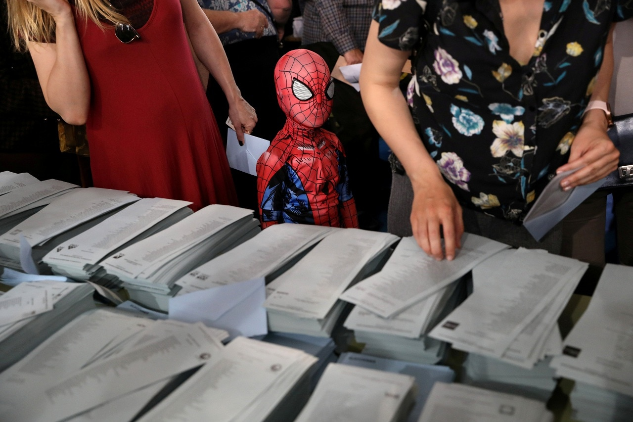 A kid in a Spiderman costume stands next to a ballot table for the European Parliament election at a polling station in Madrid, Spain, May 26, 2019. REUTERS/Susana Vera