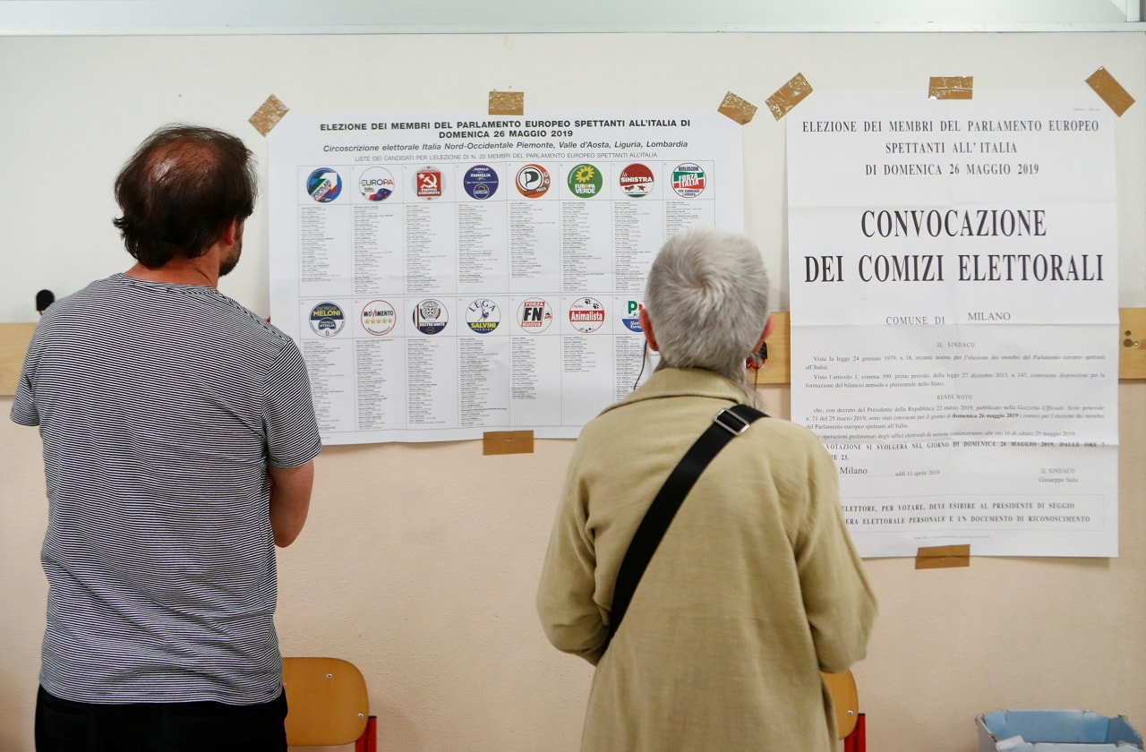 People read electoral leaflets during the last day of the European Parliament elections in Milan, Italy May 26, 2019 REUTERS/Alessandro Garofalo