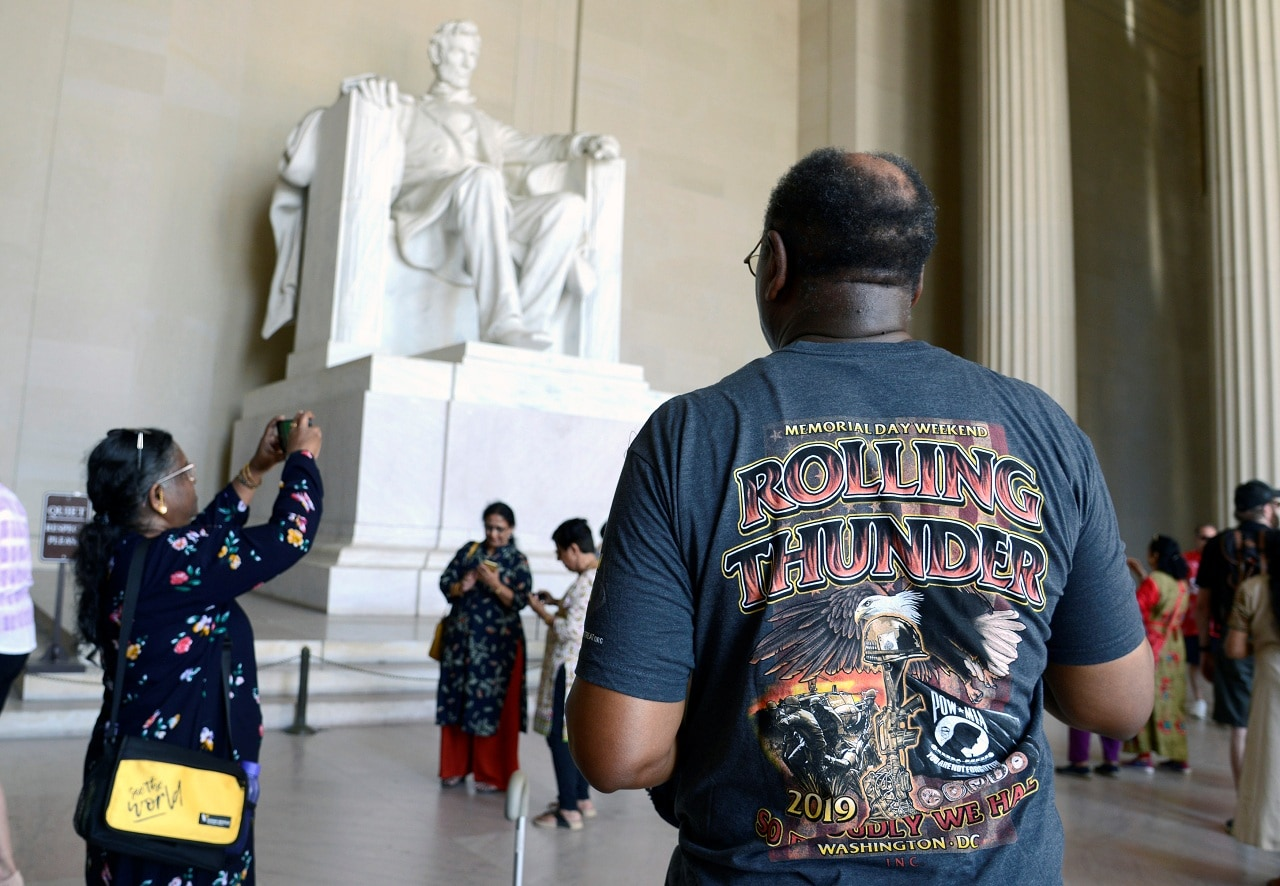 A motorcycle rider in a Rolling Thunder t-shirt joins tourists at the Lincoln Memorial prior to the start of the 32nd Annual, and possibly final, Rolling Thunder