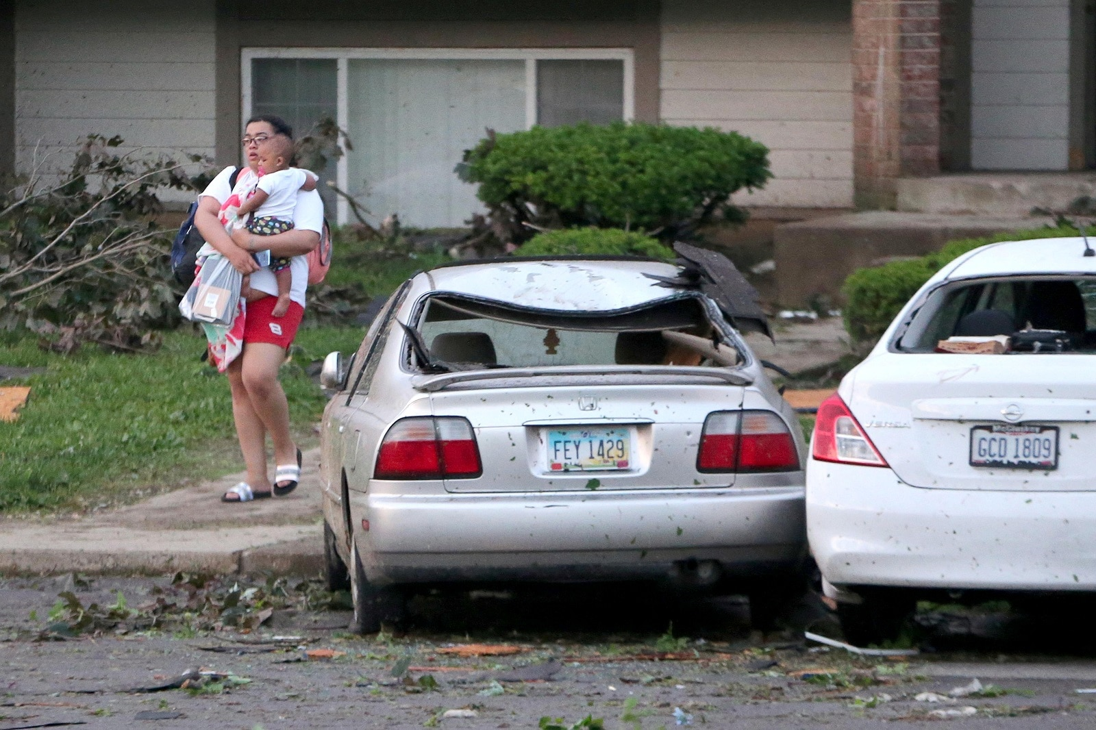 A woman leaves her apartment with a small child the morning after a tornado touched down overnight in Trotwood near Dayton, Ohio, US May 28, 2019. REUTERS/Aaron Josefczyk