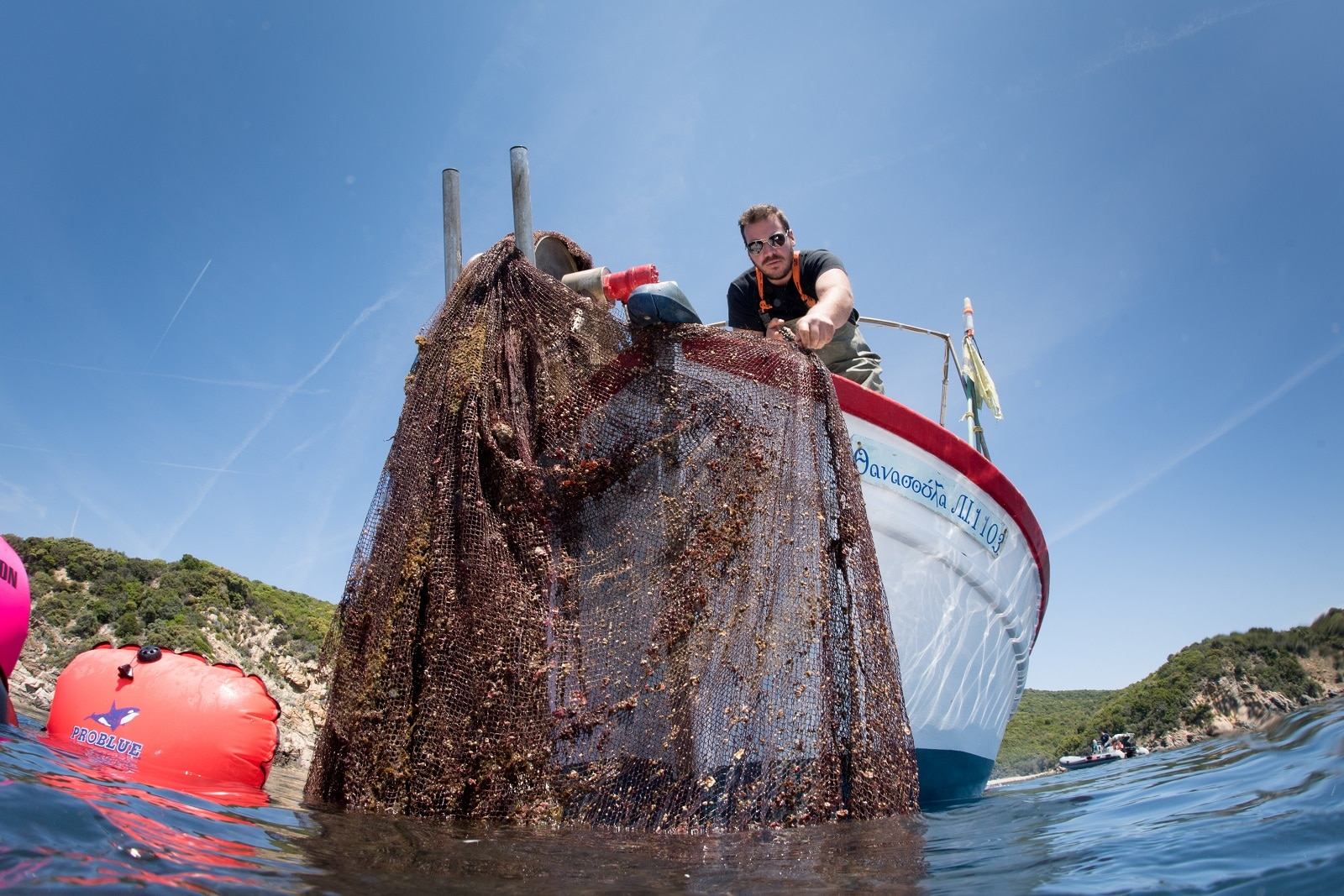 A man pulls a ghost fishing net out of the water, in the village of Stratoni near Halkidiki, Greece, May 18, 2019. Cor Kuyvenhoven/Ghost Fishing Greece/Handout via REUTERS