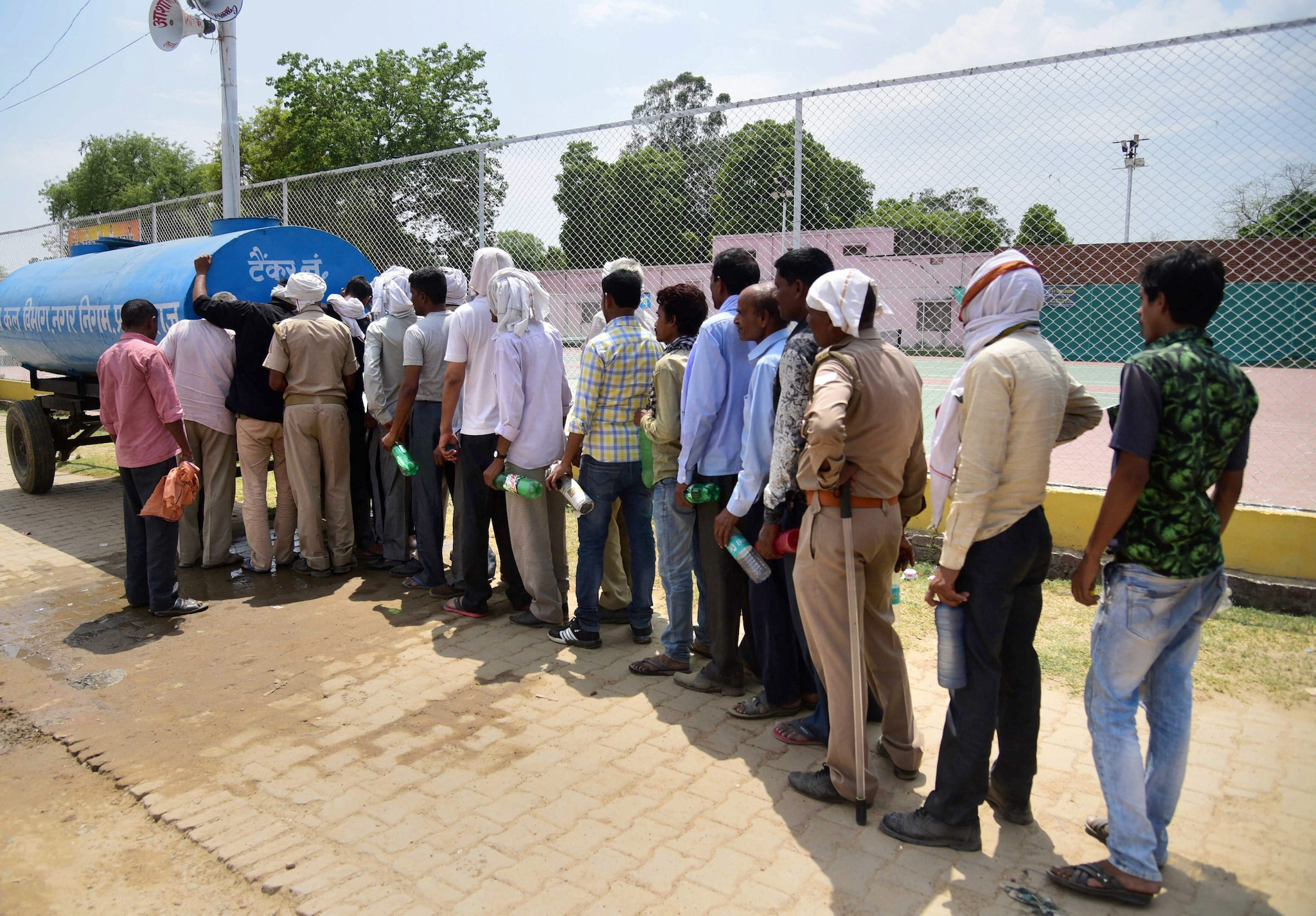 Polling staff stand in a queue to take water from a tanker, in Prayagraj, Saturday, May 11, 2019. (PTI Photo)