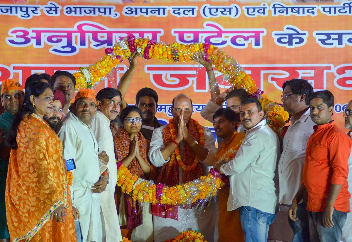 Senior BJP leader Rajnath Singh and NDA candidate from Mirzapur seat Anupriya Patel being garlanded during an election campaign rally ahead of the final phase of Lok Sabha polls, in Mirzapur. (PTI Photo)