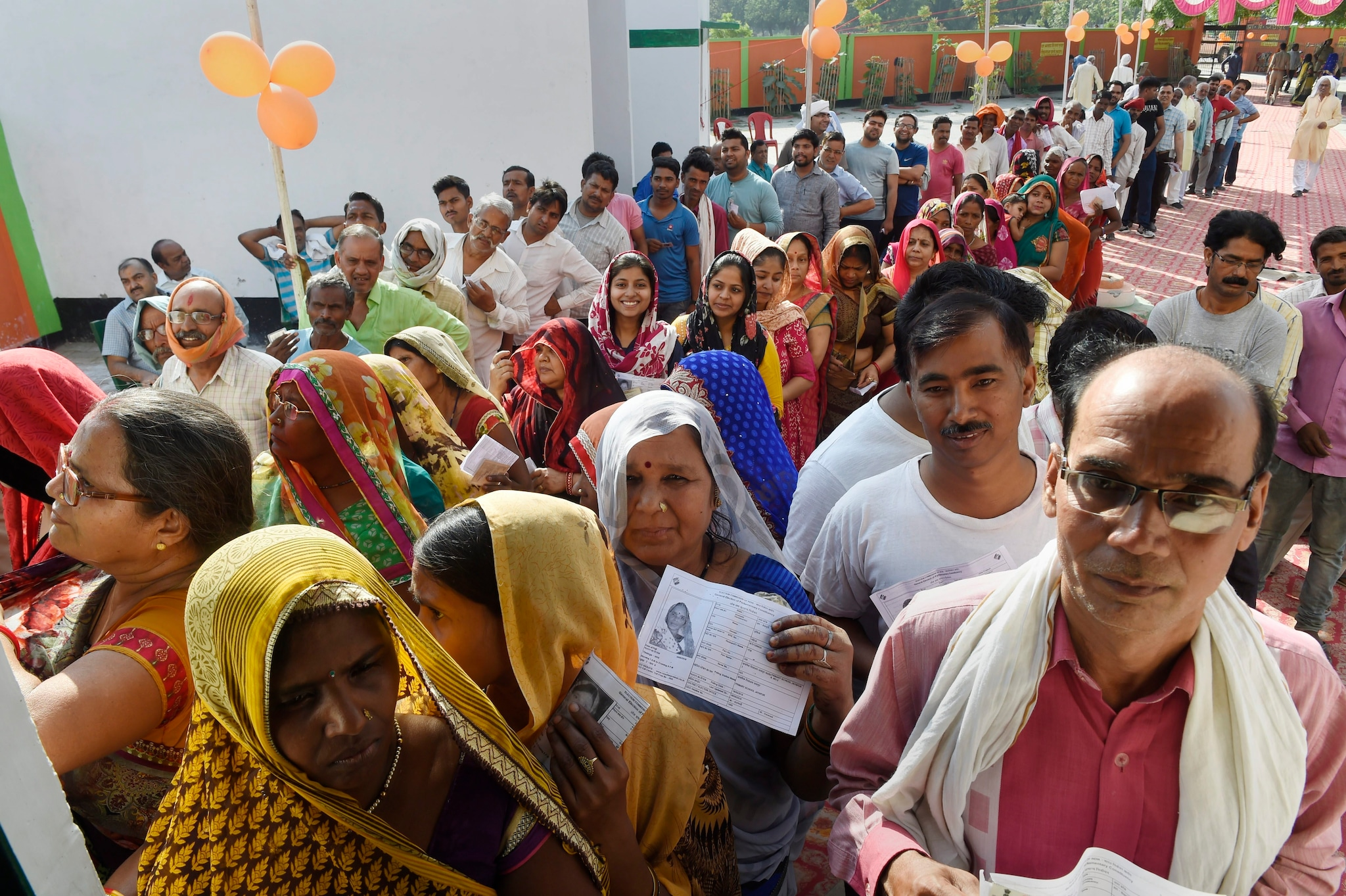 Voters wait in queues to cast their votes at a polling station, during the seventh phase of Lok Sabha elections, at Jayapur village in Varanasi, Sunday, May 19, 2019. Jayapur, is one of the villages adopted by Prime Miniter Narendra Modi during a drive which began in 2014 under the Sansad Adarsh Gram Yojana.