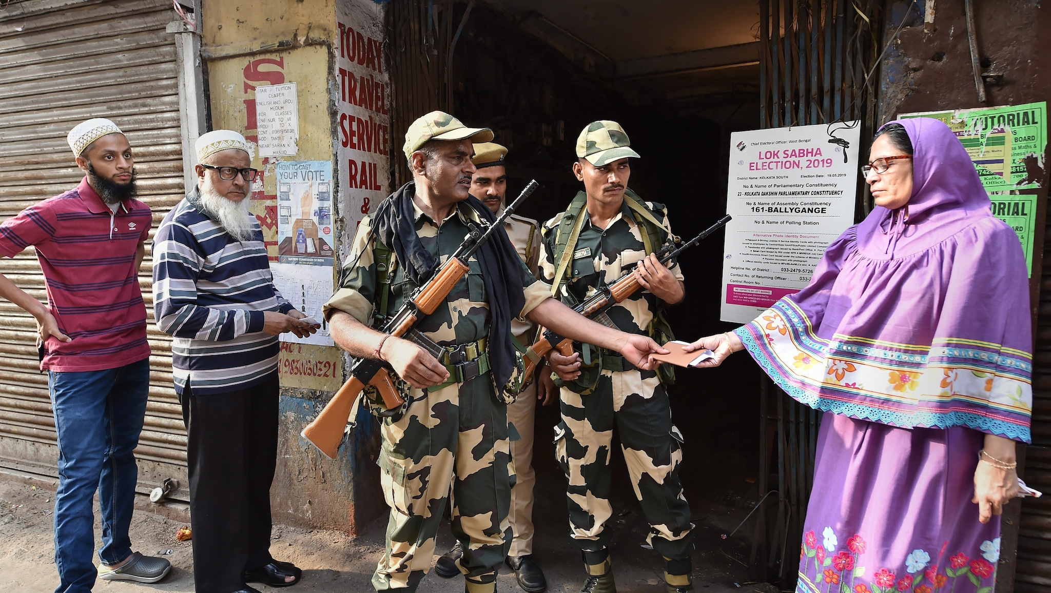 Security personnel check the identity card of a voter outside a polling station during the seventh phase of Lok Sabha elections, in Kolkata, Sunday, May 19, 2019. (PTI Photo)