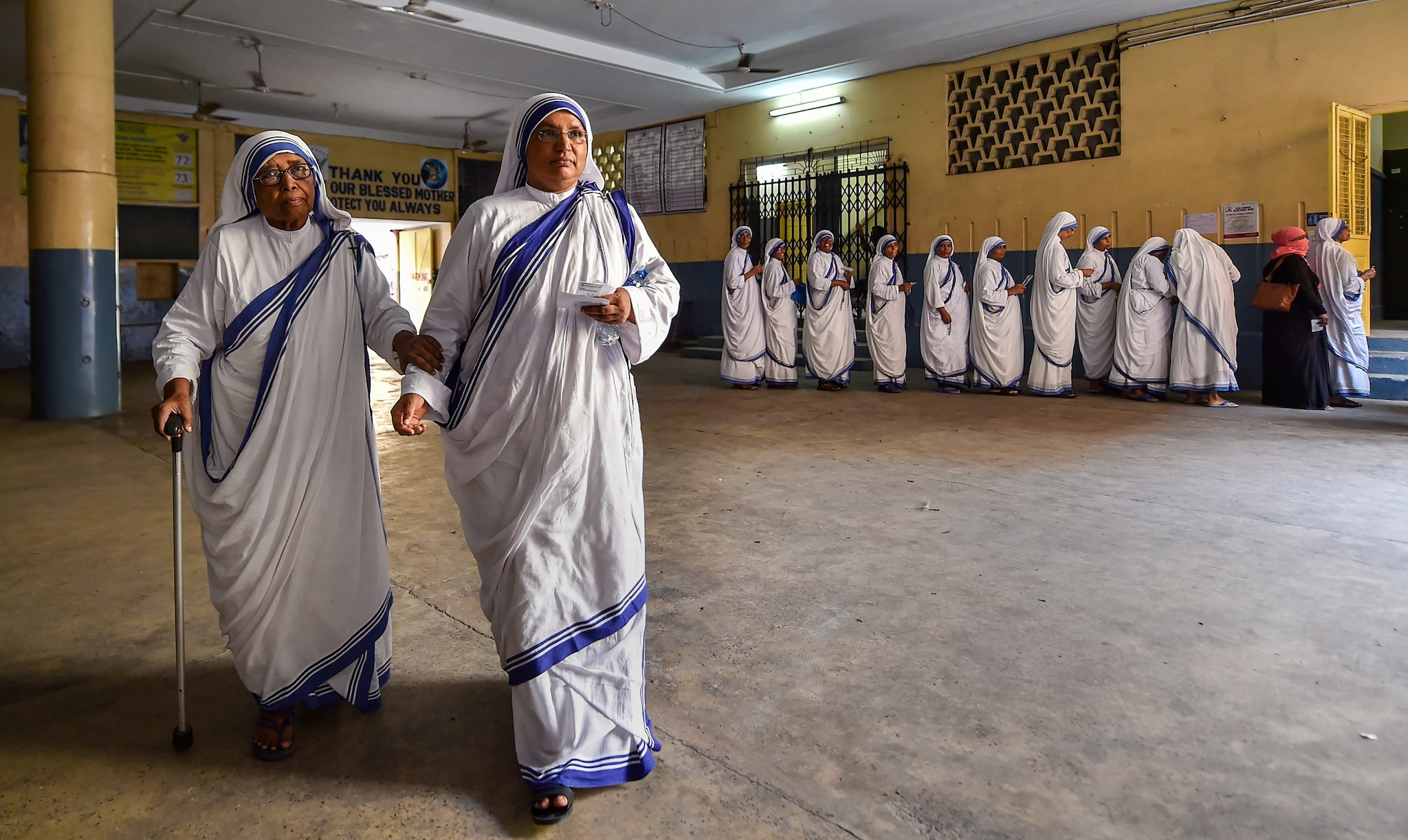 An elderly nun is assisted by the other nun as she arrives to cast her vote at a polling station during the seventh phase of Lok Sabha elections, in Kolkata, Sunday, May 19, 2019. (PTI Photo)