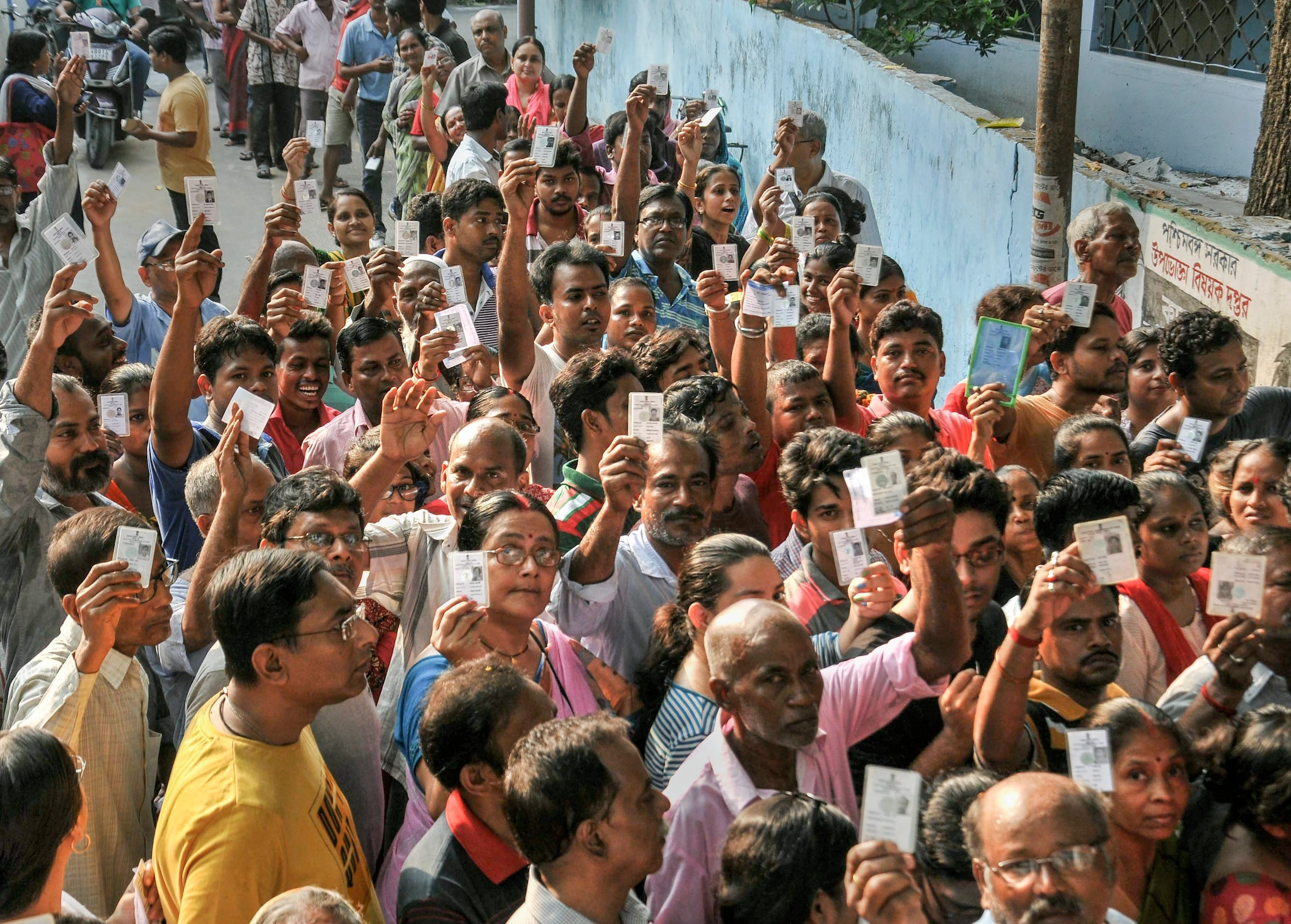 Voters wait at a polling station to cast their votes for the seventh and last phase of Lok Sabha polls, in Kolkata, Sunday, May 19, 2019. (PTI Photo)