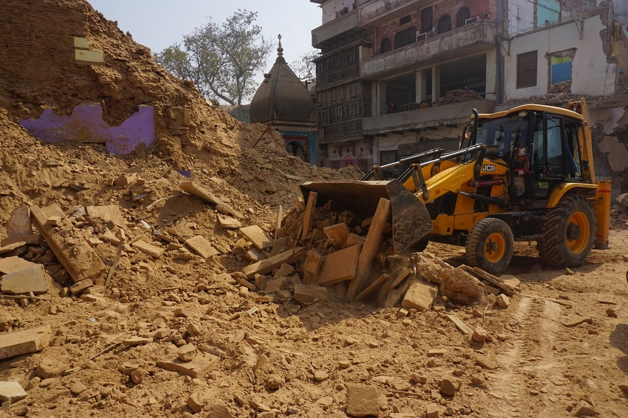 An excavator removes the rubble of demolished houses near to the Kashi Vishwanath Temple, Varanasi in Uttar Pradesh.