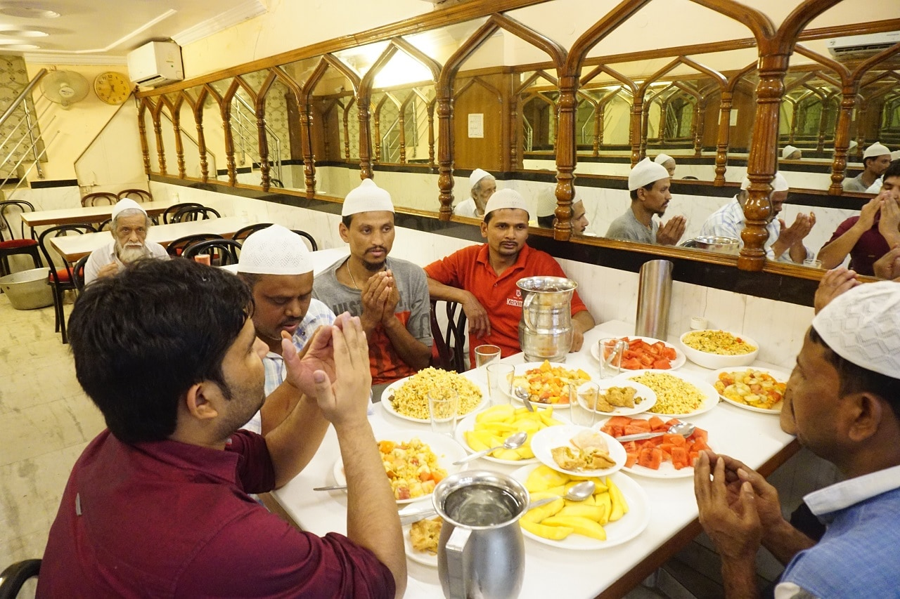People pray before breaking their fast at a restaurant near Jama Masjid, in the old quarters of Delhi