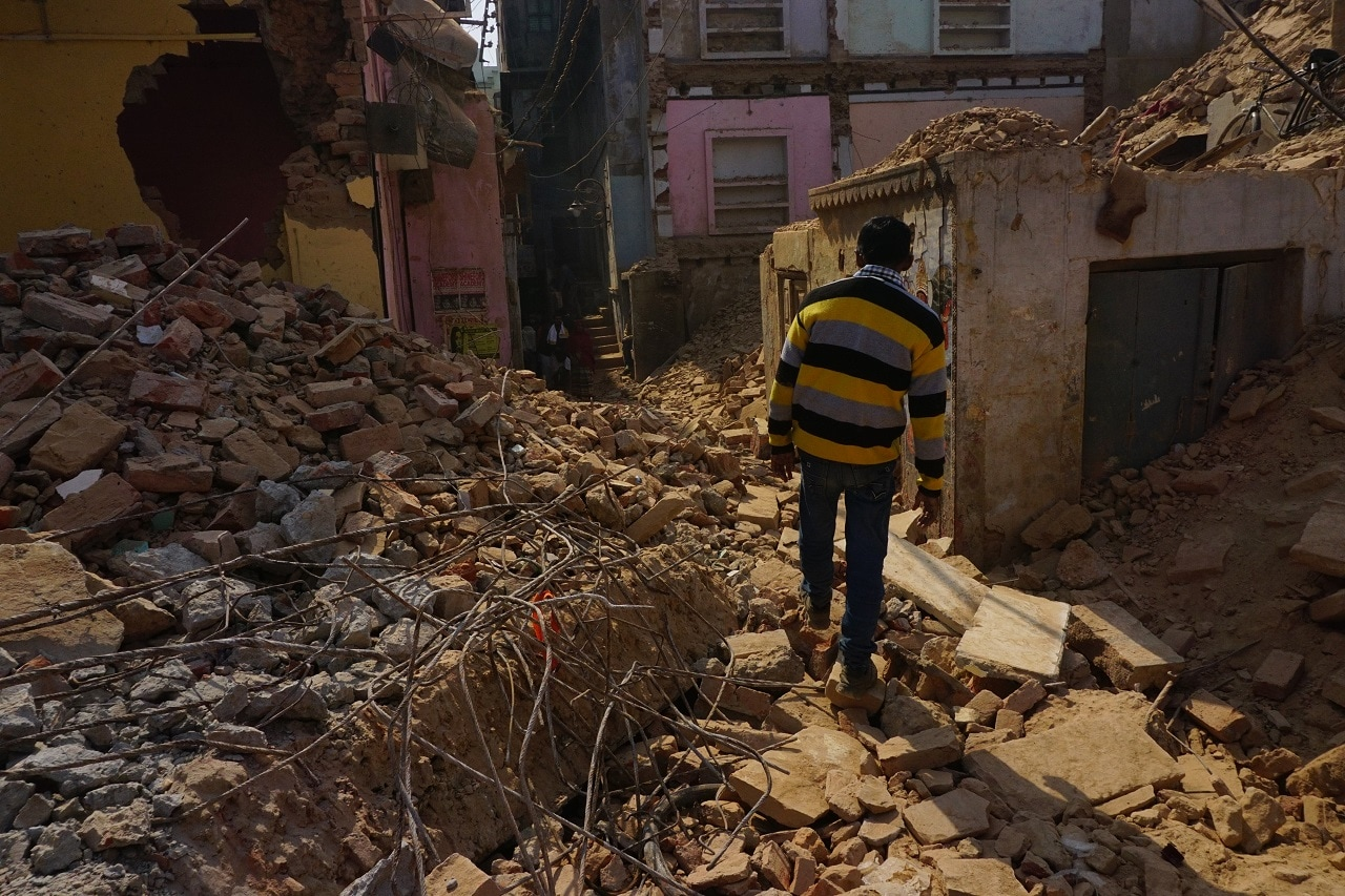 A man walks through debris from the demolition of houses and temples near to the Kashi Vishwanath Temple, Varanasi in Uttar Pradesh.