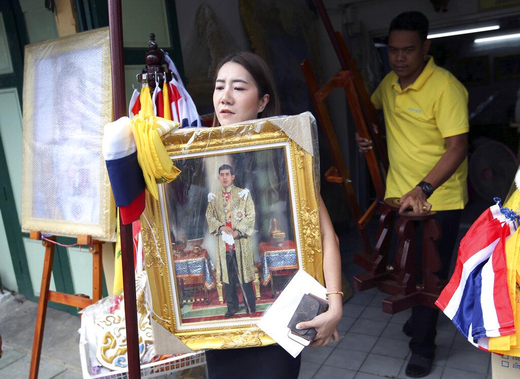 A Thai woman buys a portrait of Thailand's King Maha Vajiralongkorn Bodindradebayavarangkun in Bangkok, Thailand, Monday, April 29, 2019. (AP Photo/Sakchai Lalit)