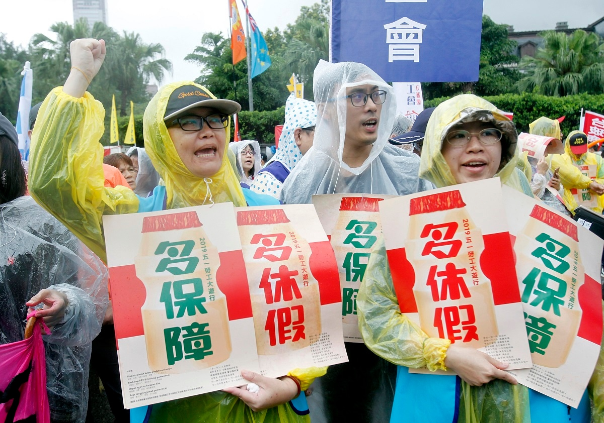 Taiwanese workers shout and hold slogans with the words