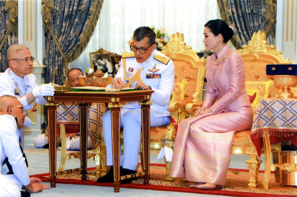 Thailand's King Maha Vajiralongkorn Bodindradebayavarangkun, center, sits with Queen Suthida Vajiralongkorn Na Ayudhya as they sign their marriage certificates at Ampornsan Throne Hall in Bangkok, Thailand, Wednesday, May 1, 2019. (Bureau of the Royal Household via AP)