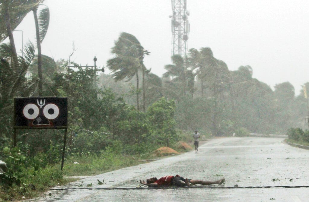 A farmer lies on the road after falling while crossing the road due to gusty winds ahead of the landfall of cyclone Fani on the outskirts of Puri, in Odisha, Friday, May 3, 2019. (AP Photo)
