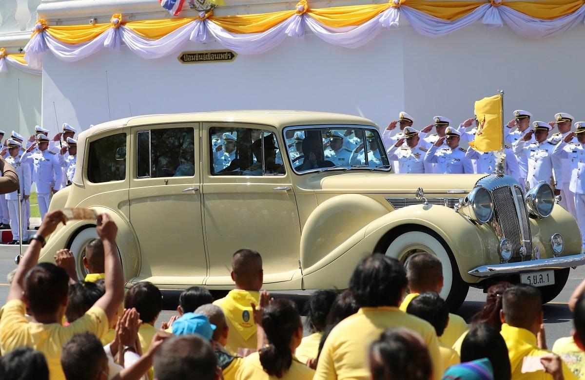 Thailand's King Maha Vajiralongkorn and Queen Suthida sitting inside a royal car drive past people. (AP Photo/Sakchai Lalit)