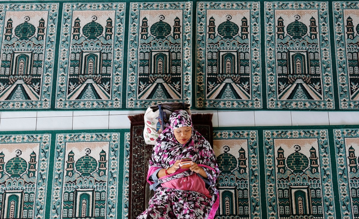 A woman rests at a mosque during the first day of the holy fasting month of Ramadan in Bali, Indonesia. Muslims around the world marked the start of Ramadan on Monday, a month of intense prayer, dawn-to-dusk fasting and nightly feasts. (AP Photo/Firdia Lisnawati)