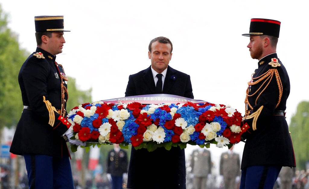 French President Emmanuel Macron lays a wreath of flowers at the Tomb of the Unknown Soldier under the Arc de Triomphe on the Champs Elysees avenue Wednesday, May 8, 2019, in Paris during ceremonies marking the 74th anniversary of World War II victory in Europe. (Christian Hartmann, Pool via AP)