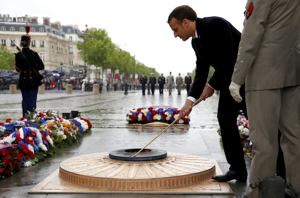 French President Emmanuel Macron lights up the flame at the Tomb of the Unknown Soldier under the Arc de Triomphe on the Champs Elysees avenue Wednesday, May 8, 2019, in Paris during ceremonies marking the 74th anniversary of World War II victory in Europe. (Christian Hartmann, Pool via AP)