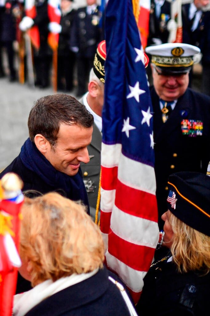 French President Emmanuel Macron meets attendees at the tomb of the unknown soldier under the Arc de Triomphe on the Champs Elysees avenue Wednesday, May 8, 2019, in Paris during ceremonies marking the 74th anniversary of World War II victory in Europe. (Martin Bureau, Pool via AP)