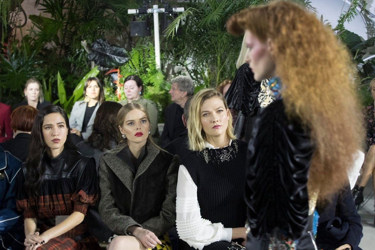 Model Karlie Kloss, second from right, watches a model walk the runway during the Louis Vuitton Cruise 2020 collection presentation. (AP Photo/Mary Altaffer)