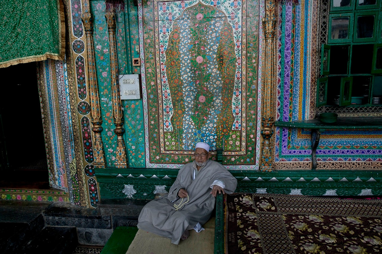 A Kashmiri man prays as he sits near the entrance of Shah-e-Hamdan Mosque in Srinagar. (AP)