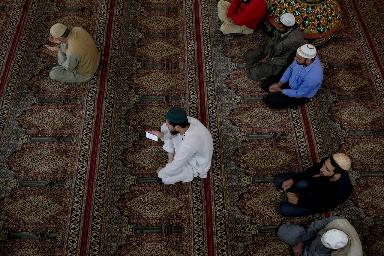 A Kashmiri man reads verses from the Quran on his cellphone inside Shah-e-Hamdan Mosque during Ramadan in Srinagar. (AP)