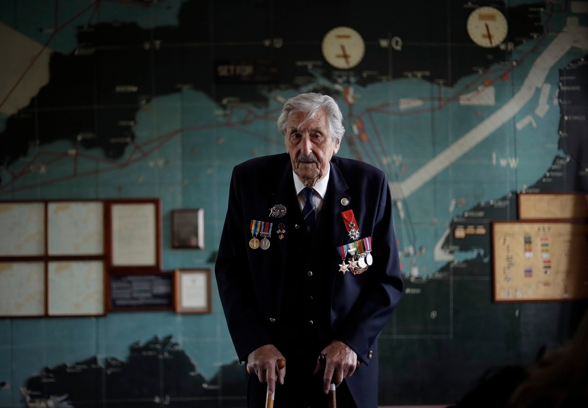 British D-Day veteran Leonard 'Ted' Emmings, who was a naval Coxswain serving on a small landing craft which landed 36 Canadians on Juno beach in France, poses for photographs backdropped by the map used to plan the Normandy D-Day landings at Southwick House near Portsmouth, England. Southwick House was the forward headquarters of the allied forces preparing for the invasion of Normandy in 1944, the nerve centre of D-Day. (AP Photo/Matt Dunham)