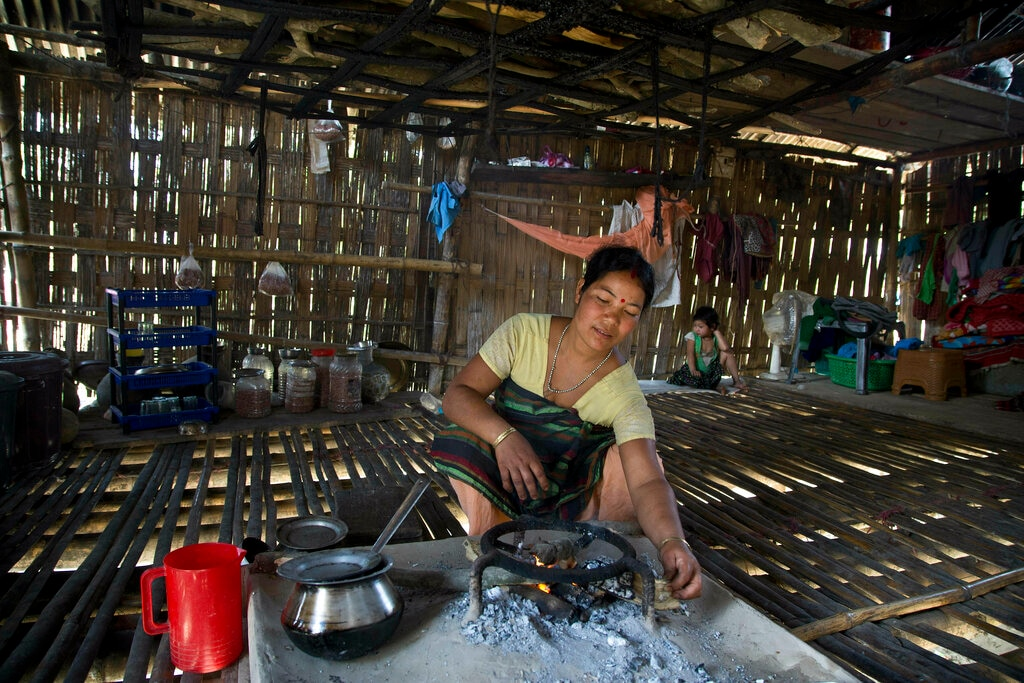 A Mishing tribal woman Jonmoni Mili, 30, makes a fire inside her house in the river island of Majuli, Assam. Mili said it makes no difference who wins the elections but that she is uneducated and wants her daughter to get an education. April 10, 2019. (AP Photo/Anupam Nath)