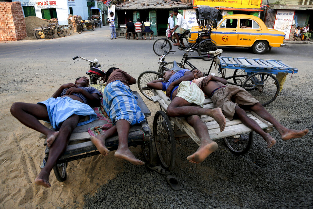 Labourers sleep on cycle carts which they use to transport goods in Kolkata. (AP)