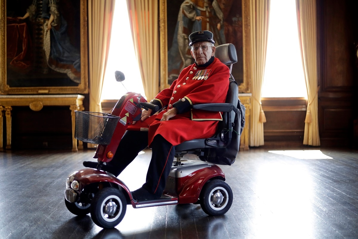 British Chelsea Pensioner and D-Day veteran Frank Mouque pose for a portrait during a D-Day 75th-anniversary event in the State Apartments at the Royal Hospital Chelsea in London. Mouque, who can't hear well now and answered media questions by reading them from a piece of paper, was a Sapper and Corporal in the British Royal Engineers. On D-Day, he landed on Sword beach and carried with him 21 pounds of explosives to blow down telegraph poles. (AP Photo/Matt Dunham)