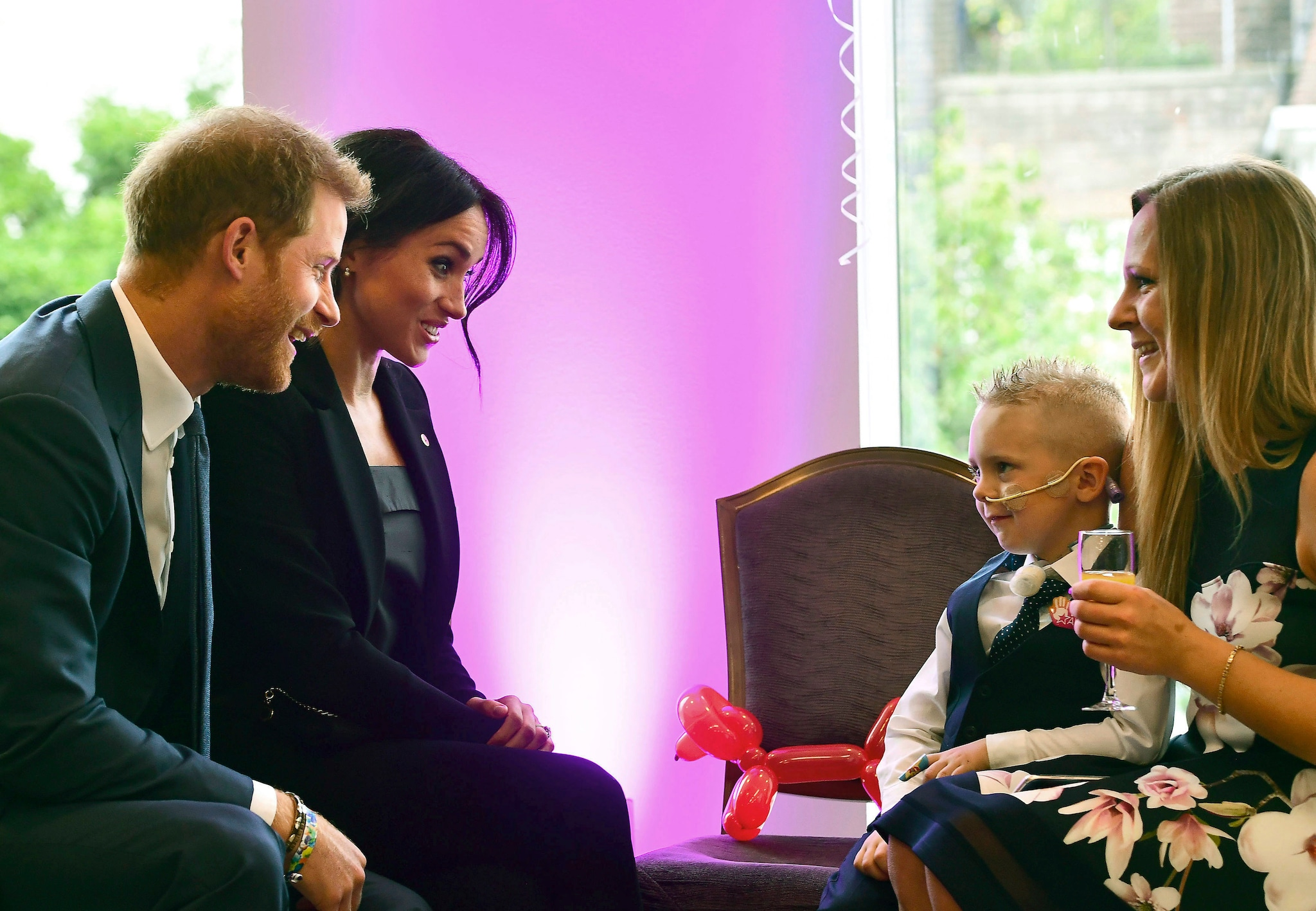 FILE - In this Tuesday, Sept. 4, 2018 file photo , Britian's Prince Harry, the patron of the charity WellChild and his wife Meghan, the Duchess of Sussex meet four-year-old Mckenzie Brackley and his mother, during the annual WellChild Awards at the Royal Lancaster Hotel in London. Sunday, May 19, 2019 marks the first wedding anniversary of the besotted couple. (Victoria Jones/Pool Photo via AP, File)