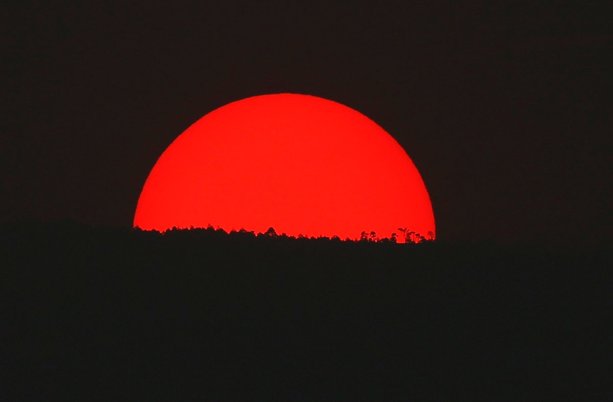 Tinted blood red by a thick cloud of smoke and pollution, the sun sets on the mountains above Mexico City. Mexico City's government has warned residents to remain indoors as forest and brush fires carpeted the metropolis in a smoky haze that has alarmed even many of those accustomed to living with air pollution. (AP Photo/Marco Ugarte)