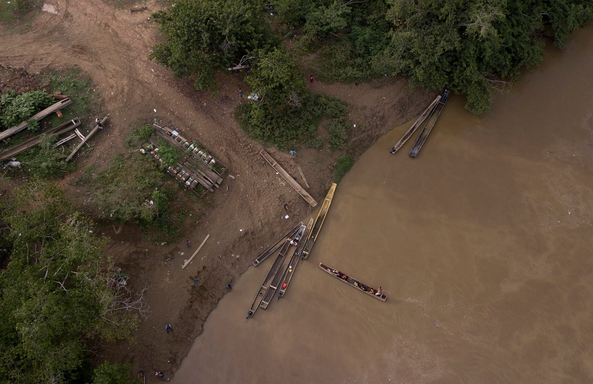 A group of migrants are boated across the Chucunaque river as they arrive in Peñitas, Darien Province, Panama. Darien's rivers can rise suddenly and furiously, and in recent weeks at least 10 migrants were reportedly swept to their deaths. (AP Photo/Arnulfo Franco)
