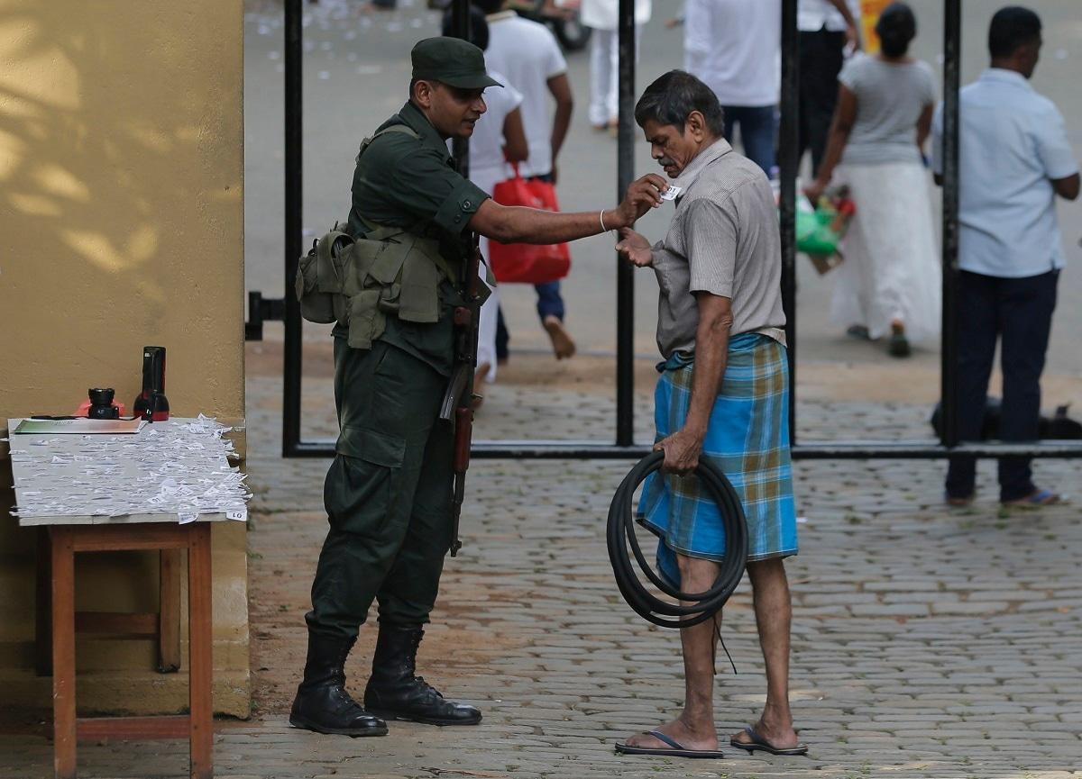 A Sri Lankan army soldier checks a man at the entrance to a Buddhist temple as devotees mark Buddha Poornima or Vesak in Colombo. (AP Photo/Eranga Jayaward