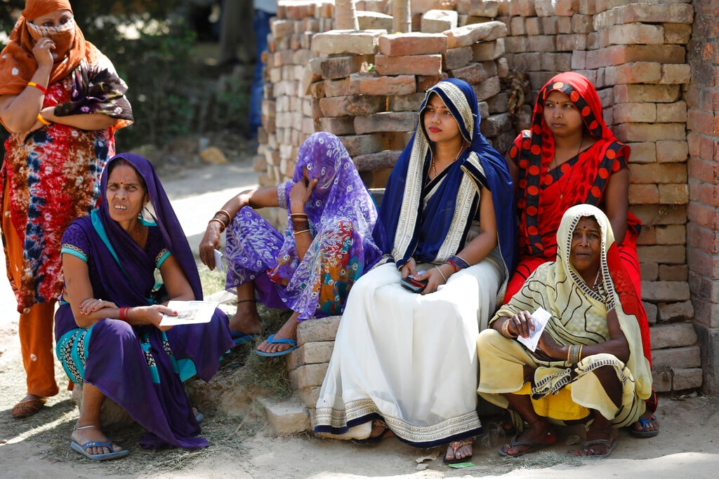 Women wait to cast their votes in the seventh and final phase of national elections, on the outskirts of Varanasi, India, Sunday, May 19, 2019.(AP Photo)