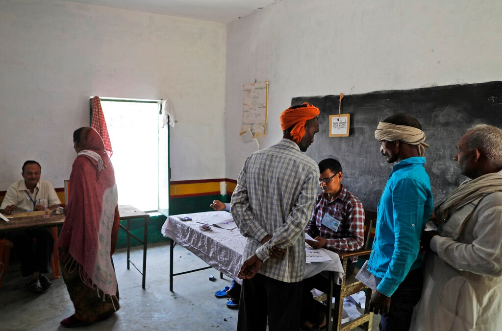 Election officers check the identity of voters before allowing them to cast their votes during the seventh and final phase of national elections, on the outskirts of Varanasi, India, Sunday, May 19, 2019. (AP Photo)