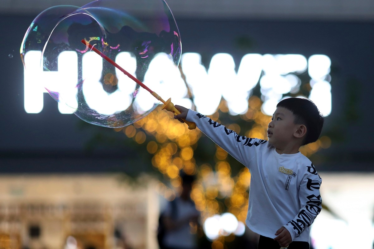 A child plays with bubbles near the logo for tech giant Huawei in Beijing. The Trump administration's sanctions against Huawei have begun to bite even though their dimensions remain unclear. US companies that supply the Chinese tech powerhouse with computer chips saw their stock prices slump Monday, and Huawei faces decimated smartphone sales with the anticipated loss of Google's popular software and services. (AP Photo/Ng Han Guan, File)