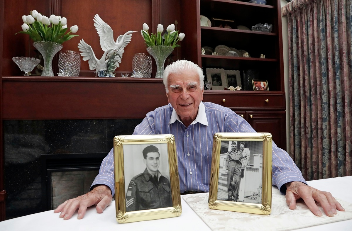 Veteran Norman Harold Kirby sits with a photo of his mother, Katherine Louise Kirby, and himself, at 17, and a post-war portrait as he poses for a photo at his home in Lions Bay, Canada. The Canadian from British Columbia had joined the army when he was only 17 and was barely a 19-year-old private when he climbed into the landing craft that would take him to shore on June 6, 1944. (AP Photo/Elaine Thompson)