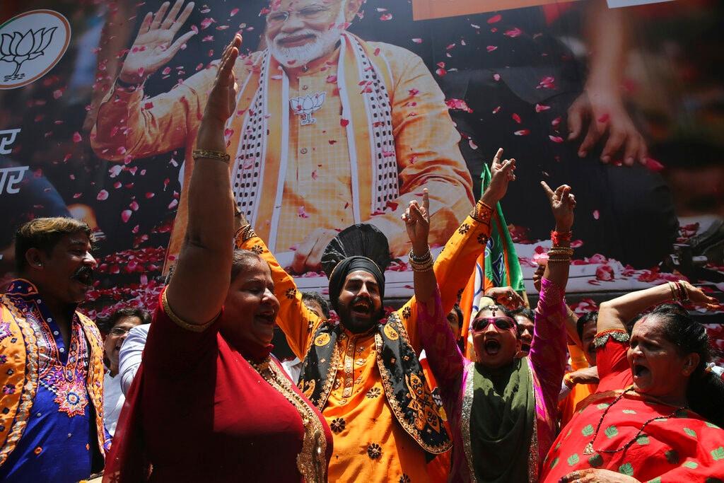 Bharatiya Janata Party (BJP) workers celebrate outside BJP headquarters in Mumbai, India, Thursday, May 23, 2019. (AP Photo/Rafiq Maqbool)