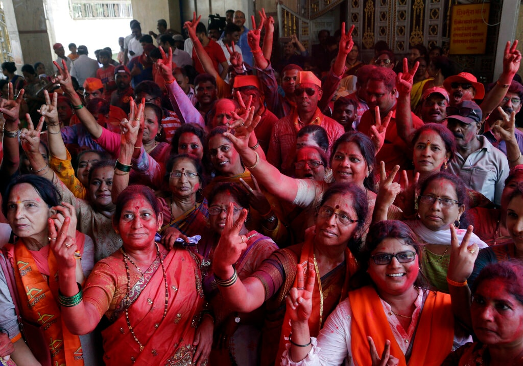 Party workers of Shiv Sena, an ally of Bharatiya Janata Party (BJP) show victory sign as they celebrate outside party headquarters during counting of votes of general elections in Mumbai, India, Thursday, May 23, 2019. (AP Photo/Rajanish Kakade)